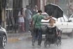 비 맞으며 휠체어 타고 가는 여성에게 우산 씌워주는 남성