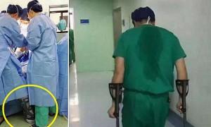 다리에 '깁스'한 채 환자 수술을 마친 한 의사의 뒷모습
