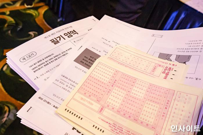 22일 오후 서울 잠실 롯데호텔서 '제2회 배민 치믈리에 자격시험'이 열린 가운데, 직원이 1교시 시험지와 답안지를 나누고 있다. / 사진=고대현 기자 daehyun@